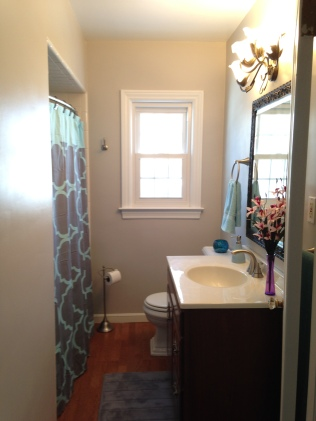 After - a lot brighter with a teal and gray theme. To stay on a tight budget we kept same light fixture, toilet, floor, and vanity. Hard to tell it's the same bathroom!